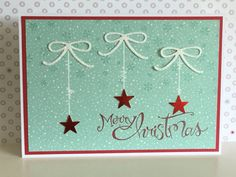 Card No 2 - a simple card using a backing paper from SUHome for Christmas which I have stamped with tiny snowflakes and the greeting. Red foil punched stars hang from die cut bows, and the 'strings' have been drawn on with a white gel pen - Julia Jordan