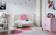 Children's room with a white crib, which has turned into a bed.  Shown with a white changing table and a pink dresser.