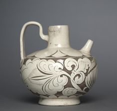 Spouted Ewer with Handle.   Northern China, Northern Song dynasty (960-1127)  glazed stoneware with carved decoration, Cizhou ware, Diameter - w:15.90 cm (w:6 1/4 inches) Overall - h:17.60 cm (h:6 7/8 inches). Purchase from the J. H. Wade Fund 1948.219. Cleveland Museum of Art.