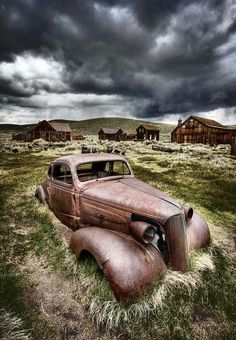 seems so dead here! An old Chevy car sits all rusted among abandoned buildings in Bodie Ghost Town under stormy skies.An old Chevy car sits all rusted among abandoned buildings in Bodie Ghost Town under stormy skies. Abandoned Buildings, Abandoned Houses, Abandoned Places, Abandoned Property, Pompe A Essence, Rusty Cars, Old Barns, Horse Barns, Ghost Towns