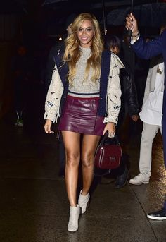 Beyonce, entering the Chanel Paris-Salzburg show in NYC in a crew neck sweater, leather mini skirt, and ankle boots