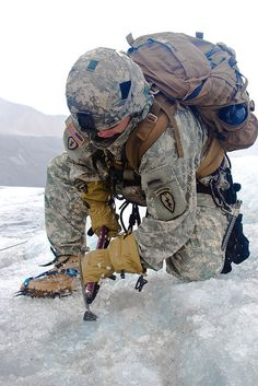A student of the Basic Mountaineering Class of the U.S. Army Northern Warfare Training Center, clears a spot on the ice to set his ice screws in for crevasse rescue operations. Photo by Staff Sgt. Brehl Garza.