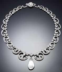 DIAMOND AND PEARL NECKLACE, LATE 19TH CENTURY. Designed as a series of graduated scrolls set with circular-, rose-cut and cushion-shaped diamonds, suspending a natural pearl drop, length approximately 400mm.