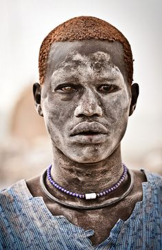 Africa | A Mundari male covered in ash and orange hair bleached in the sun from washing it in cow urine. Terakeka, Bahr al Jabal, Sudan. | ©Tom McShane