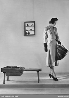 Modell i ljus klänning, uppslagen hatt, pälsmuff, handskar och pumps. Hylla på väggen och bänk på golvet. Foto: Sten Didrik Bellander, 1950-55