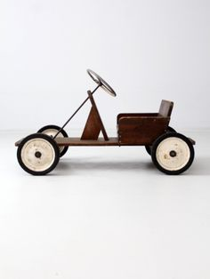 """A vintage toy riding car. The large wood car """"cart"""" has a metal frame with wood…"""