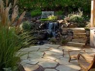 Use a hillside garden's natural contour changes to add dimension to a landscape. In this example, stone stairs draw the eye up to a higher seating area.