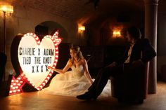 Bride and groom with vintage lighting and signage in The Vault Bar. Photography by Sean Elliot Photography.