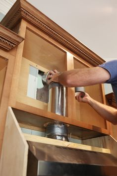 raise up cabinet, install vent below, build wood cover around vent system to blend into cabinets