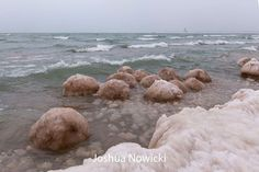 Ice boulders with the lighthouse in the distance . . . January 6, 2017 in Saint Joseph, Michigan.  Photo by Joshua Nowicki - Photography