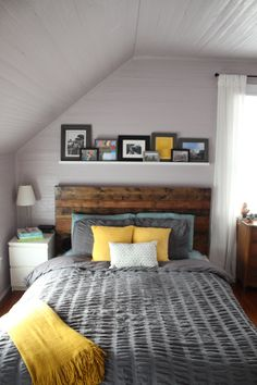 to die for: the headboard. the shelf of prints. the gray. the yellow. the sloped ceilings.
