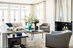 In the living room, interior architect Chad Eisner created a floating marble fireplace, which is flanked by Holly Hunt club chairs and a sofa, coffee table and accent tables all by C.W. Eisner.