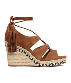 PREMIUM QUALITY. Suede sandals with wedge heels covered in braided jute cord, lacing at the front with long straps with suede tassels at the ends that tie around the ankle, leather linings, fabric insoles and rubber soles. Platform front 2.5 cm, heel 10 cm.