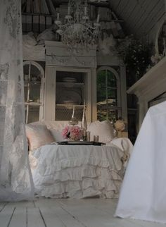 White ruffled bedding, mercury glass, lace curtains, antique white tall furniture, white antique floorboards, pink flowers, chandelier, white antiqued mantle