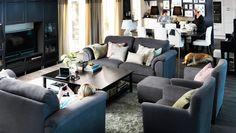 Harmaat sohvat ja lepotuolit suuressa olohuoneessa