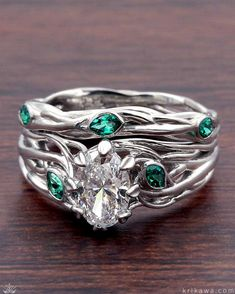This organic design features brilliant emerald leaves suspended atop the climbing branches that make up the bands. Leaf prongs hold the pear cut diamond center stone! Customize your bridal set in your choice of metals and gemstones or diamonds!