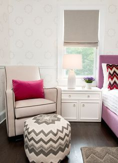 Kid's bedroom reading nook boasts a beige glider with black piping layered with a raspberry pink velvet lumbar pillow across from a white and gray chevron pouf framed by walls clad in Weitzner Wallpaper trimmed with chair rail.