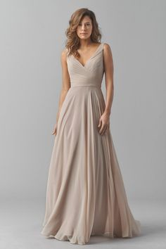 Sweep into the wedding festivities in the softly shirred Watters Karen 8542i bridesmaid dress. This sleeveless, full-length gown is styled in double-lined crinkle chiffon, creating a delicate effect. The shirred, surplice bodice features a deep V-neckline and V-back. The waistline is emphasized with a chiffon sash that ties in the back. The long A-line skirt floats in filmy layers to the floor.