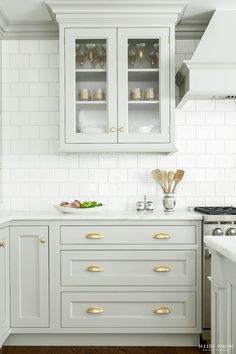 Pale grey cabinetry with white subway tile and gold hardware. Love!
