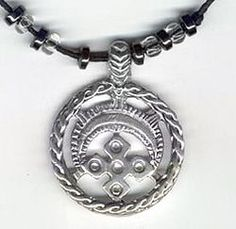 Circular crescent pendant combines solar & lunar symbolism. Between the horns of the crescent moon is a symbol of the sown field - a sign of fertility and motherhood -  a universal protection charm for women. The pattern on this crescent reflects the cosmogonic view of the Slavs, associated with fertility magic -  the heavens with the sun in the middle, earth and streams beneficial rain, indicated by oblique rows of small grains.