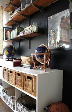 This actually ugly shelving system painted black on a black wall really makes a difference. Nice industrial look.
