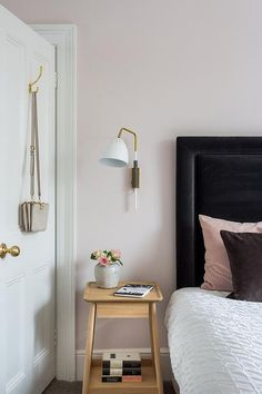 Feel right at home in this welcoming bedroom equipped with a white and gold sconce mounted to a blush pink wall above an oak nightstand placed beside a bed supported by a black velvet headboard and dressed in white ruched bedding topped with blush pink and black pillows.