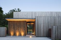 """As for material, Masi opted for a select grade of knotty Western Red Cedar on the exterior, he paired beautiful 12"""" wire brushed boards with custom stainless steel clip for siding, fencing and the outdoor shower. He also used that same combo to panel the kitchen, living room, dining area, hallways, guest room and guest bathroom."""