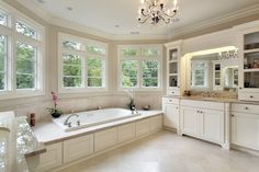 Another example of large bathtub seated in window alcove, this bathroom features white painted wood all around and high ceiling with chandelier.