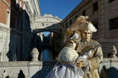 Costumed revellers pose in front the Bridge of Sighs during the carnival in Venice. (from The Guardian)