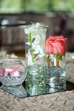 Cheap DIY Wedding centerpieces! Buy different sized vases and clear stones from the dollar store, and buy flower frogs at Michael's.  Decide on flowers (we chose orchids, roses and daisies), trim flowers to size, and stick on frogs.  Cover with stones and then water, and even add a floating candle on top of the orchids! Super cheap and beautiful <3 Nat