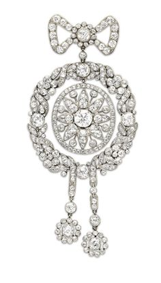 A BELLE EPOQUE DIAMOND BROOCH, BY CARTIER  Designed as an old European-cut diamond bow, suspending an old European and rose-cut diamond laurel wreath, set with a central old European and rose-cut diamond openwork plaque of sunburst design, with old European-cut diamond articulated ribbon tassels with diamond cluster terminals, mounted in platinum, circa 1908 Signed Cartier, Paris