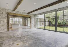 """Unfinished or do you like this concrete floor? Either way, those windows are incredible!"" Concrete floors. Steel frame glass windows. Interior brick. Reclaimed wood beams."