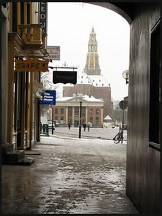 """Door het Koude Gat, Groningen. De naam is een verbastering van """"Corps de Garde"""". Te zien zijn Albert Heijn in de Korenbeurs (A-Kerkhof) en der Aa kerk."""