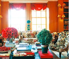 Tory Burch's stunning orange library in her Upper East Side apartment at The Pierre. Love the fearless red shades, the double double-sconces (hahaha quadruple scones?), the topiaries, and that little tufted tiger chair. Fabulous.