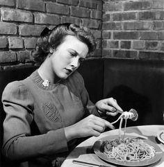 Woman eating spaghetti in restaurant. New York, 1941