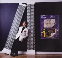David at his first solo art exhibition 'New Afro/Pagan And Work 1975-1995' at The Gallery, 28 Cork Street, London, which ran from 18th-29th April 1995. The two vertical pilasters with a white ornate Capitol base were covered with his wallpaper design 'British Conflicts Series: No. 1 - Art'.