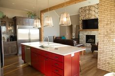 Mouldings | proof positive that mixing cabinet colors with wood and stone is a step in the right direction.  here, gray perimeter cabinets and prefinished trim highlight the fun of a bold red island; who says the Midwest is afraid of color? | Bayer Built Woodworks, Inc.