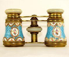 A delightful pair of antique mid 19th century French enameled opera glasses. In a gorgeous pale blue color, Celeste blue and accented throughout with charming 'jewels' or beads of translucent pink enamel! Sprinkled throughout with small silver stars and silver trimming. Adorned by four medallion cartouches accented by clusters of brightly painted flowers. These stunning opera glasses exhibit such fine craftsmanship, typical of enamellists residing in Sevres. From The Antique Boutique