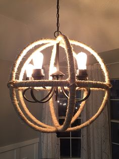 """After - Dining Room (with new DIY'ed orb light!) as of May 2015 // DIY rustic-transitional orb light - made with three 23"""" quilting hoops, sisal rope from Lowes and the existing satin nickel chandelier that we spray painted with Rustoleum's oil rubbed bronze. The """"metal finial"""" on the bottom is actually made of wooden toy car tires from Hobby Lobby, glued together. To disguise the threads that were exposed when we removed the old frosted glass light sconces, we glued (with E600 glue) 1.5""""…"""