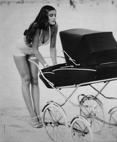 Sexy mother in a swimsuit with a vintage stroller