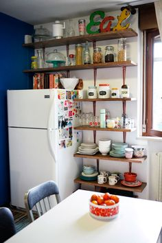 Open shelving with butcher block wood and painted metallic shelf brackets = the coolest!