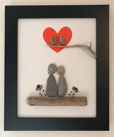 Pebble art of couple sitting on driftwood with pebbles flowers on either side with two love birds on a branch inside a red heart. Frames in a black frame with outer dimensions 12x10.