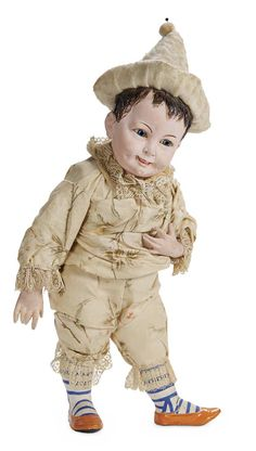 Rare French papier-mâché character doll candy container in original silk costume, separates at the waist for access to hidden candy container center, circa 1890.
