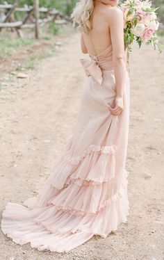 Romantic and ethereal blush wedding dress with lovely ruffled train.