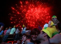 Fireworks are displayed over Lebanese soccer fans who have gathered to watch the first soccer match of the World Cup between Brazil and Croatia, at a fan park in downtown Beirut, Lebanon, Thursday June 12, 2014. (AP Photo/Hussein Malla)