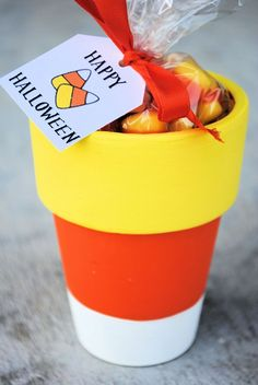 I love these candy corn flower pots! Make for Halloween morning surprise!