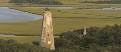 """Affectionately known as """"Old Baldy,"""" The Bald Head Island Lighthouse is North Carolina's oldest standing lighthouse. Its appearance is the result of decades of patchwork repair and 141 years of service."""