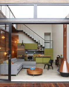 Lighting along the wall is from fixtures made of plumbing pipe. Atrium House in Williamsburg, NY by MESH Architects.
