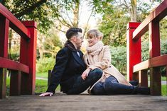 Couple sit on the red Monet bridge in Bournemouth gardens