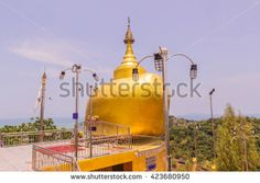 Phuket, Thailand - April 25, 2016 : The replica of Phra That In-Kwaen (Hanging Golden Rock) at Koh (islands) Sirey temple, Phuket, Thailand. It was built by Myanmar Buddhists who work in this region. - stock photo